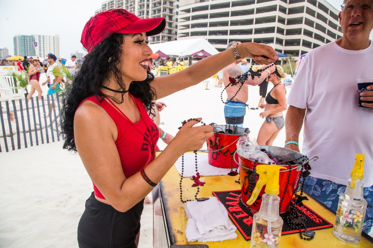 Female bartender handing out Fireball beads on beach